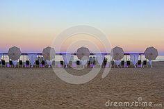 Shining sea beach sunset with beach umbrellas, Costa Darado, Spain