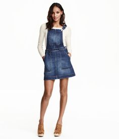 Short bib overall dress in washed stretch denim with adjustable suspenders. Buttons at sides, bib pocket, side pockets, and back pockets. Unlined.