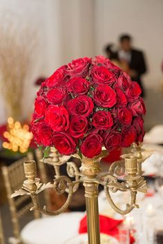 Our centerpieces- red roses in an antique candelabra. Red, beige/champagne wedding.