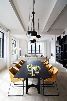 8 Modern Dining Rooms \\\ This Piet Boon-designed apartment is located in a building that used to be home to offices in NYC. With white walls and black details, this light-filled dining room is home to mustard colored chairs that add warmth and life to the minimalist space. Photo by Paul Barbera