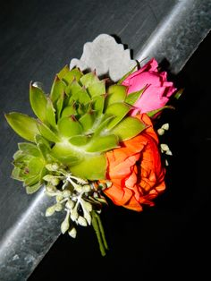 Groom's boutonniere with mini succulent, ranuncula and spray rose.