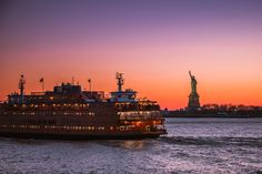 Staten Island Ferry sailing by Statue of Liberty at dusk by Javan Ng @javanng by newyorkcityfeelings.com - The Best Photos and Videos of New York City including the Statue of Liberty Brooklyn Bridge Central Park Empire State Building Chrysler Building and other popular New York places and attractions.