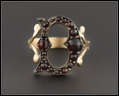An initial ring like no other, this letter D ring was created from an antique silver pin and set onto a 14k gold band with split shoulders.  The ring features rose cut bohemian garnet stones and is unmarked, but acid tests for 14k gold. The overall condition is excellent; however, under magnification you can see a bit of resin that was likely used to re-set one of the stones.  The ring is currently a size 3.5, but it can be re-sized free of charge. Etsy