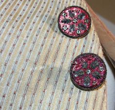 Detail of frockcoat material and buttons decorated with mirrors and red sequin flowers with five petals. Late 18th century, Spain.  Inventario 00322  Museo de Albarracín