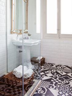 Baño de estilo retro con suelo hidráulico, ducha y lavabo vintage