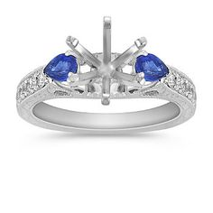 Two stunning pear-shaped sapphires, at approximately .50 carat TW, are accented with six round diamonds, at approximately .22 carat TW, in this vibrant vintage inspired engagement ring.  Crafted in quality 14 karat white gold, the center stone of your choice will dazzle in this glorious setting.  The total gem weight is approximately .72 carat.