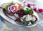 A small platter of 2 open-face Danish sandwiches, smoked salmon and liverwurst, served outside on the patio