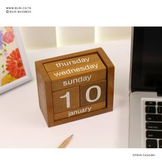 Wooden blocks in a tray that can be flipped to keep up with the month and day. The blocks are painted in distressed natural wood with black lettering in
