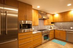 Favorite kitchen.  Bamboo cabinets, stainless appliances.  This gorgeous modern kitchen features all the sleek efficiency of the style, but the warm brown of the wood cabinets and the brown tile backsplash give a welcoming glow to the space.