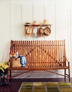 In the front entry hall, a collection of hats hangs above a contemporary bentwood garden bench.