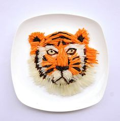 Tiger created with chopped carrots, white radish, and prunes.