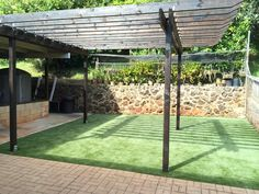 SYNLawn artificial turf for a backyard patio in Honolulu.  Built in place pergola stained mocha brown .