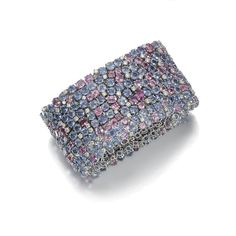SAPPHIRE AND DIAMOND BRACELET, MICHELE DELLA VALLE The wide band of open work mesh design, set throughout with variously-shaped sapphires of pink and blue tints, interspersed with brilliant-cut diamonds, length approximately 180mm, maker's marks and numbered.