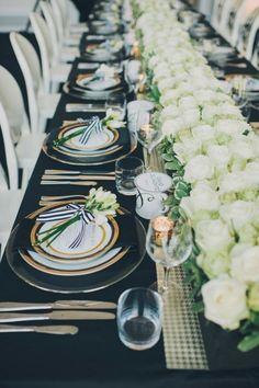 schwarze Tischdecke und weiße Rosen dem Tisch entlang