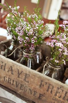 Milk bottles w/flowers in an old crate. Gorgeous centerpiece.