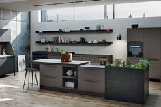 SieMatic's versatile Urban kitchen line is tailor-made for cosmopolitan living. Shown are the oak sideboard (far left) in matte black; cabinetry in Umbra matte lacquer with a countertop of Piatra Grey composite; and an herb-garden unit in Nero Assoluto granite. All elements can be customized in any SieMatic material and color; systems from $40,000. siematic.us, 215-604-1350