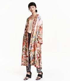 Calf-length kimono in woven viscose fabric with a heavy drape and a printed pattern. Side pockets, pleat at back with contrasting section, and removable tie belt at waist. Long, wide sleeves.