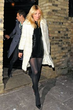 Kate Moss in a shaggy cream coat tossed over a black sequin mini dress, tights and pointed heels