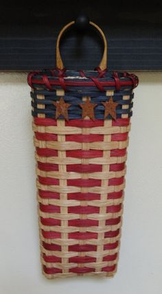 This Americana wall basket would be a nice added touch to your red white and blue decor. Hang it on an inside door or in any room of your home.  This Americana basket is stained with a oak stain and is embellished with 3 rusty tin stars. It has a sturdy wood handle for hanging and a solid woven base.  Measures approx: 3 1/2 W 5 L 12 H at rim
