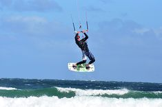A kite surfer taking to the air.