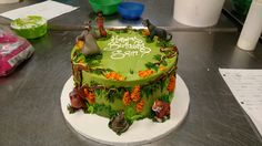 A Jungle Book cake with a hand iced jungle scene and plastic figurines.
