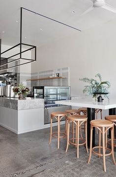 The cafe interior has a gentle pastel palette with a base of warm grey and soft pink, pierced by clever incisions of royal blue.