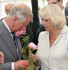 Prince Charles, Prince of Wales and Camilla, Duchess of Cornwall smell roses during a visit the 132nd Sandringham Flower Show at Sandringham House on July 31, 2013 in King's Lynn, England.