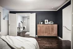 Dark grey bedroom wall in an elegant Swedish apartment in shades of grey. Entrance.