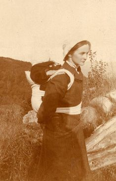 From one og our our old family albums. Young woman carrying a child in baby carrier. Eastern Norway, probably some time around 1900