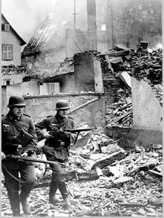 German soldiers move through a devastated French village.