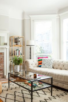 Top 10 Home Tours of 2015 #theeverygirl // living room with Moroccan rug // tufted couch // serape pillow // colorful accents // glass coffee table // gold bookshelf