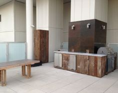 Custom Outdoor Kitchen with  Reclaimed Wood Cabinets, Carrara Marble Countertops and Oxidized Steel Wall