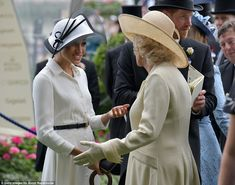 The new Duchess of Sussex was seen having an animated conversation with the Duchess of Cornwall, who also opted for an elegant ensemble