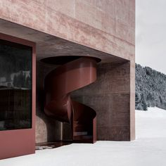 A red balustrade curls around this staircase, which is set into a niche at one end of an Alpine fire station. Its bold russet colouring offsets the muted pigment of the red concrete building, designed by Italian studio Pedevilla Architects.