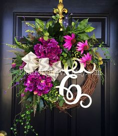 Gorgeous Spring Door Wreath! Perfect for greeting your guests to your home, with this one of a kind door wreath.  Made up on an 18 grapevine wreath with moss, mixed flowing greenery with gorgeous purple hydrangeas and purple black eyed susans. A decorative 12 ivory script monogram and a gray chevron jute bow make this wreath one of a kind.  Measures approx 28x 25 x 7( tip to tip).  NOTE: Ribbon shown is currently unavailable. Choose the letter you would like by leaving me a note when…