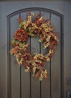 An original design by An Extraordinary Gift ©  Love, Love, Love this! I used an 18 grapevine base and filled it with artificial twigs, berry branches, artificial eucalyptus, and pinecones. I also used a large brown peony bloom as a beautiful focal point. I just love how the twigs extend and give it such a natural feel.  This design measures approx. 20 in diameter and extending up to 35 and would look wonderful on any door or wall in your home.  Giving An Extraordinary Gift is perfect for all…