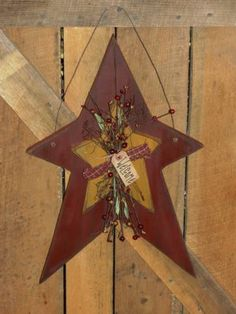 I have hand painted thisstar in the color in burgundy with black underneath and added a top star in mustard with black underneath.  I have added twigs, berries, homespun bow and grungy tag. It has been distressed for more of a primitive appearance. Niceprimitive accent piece for yourhome decor.  Measures approx 15 x 23   Homespun and Berries will vary and will go with your star color choices.