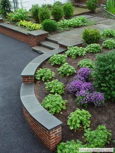 Rock Fence Designs | Curved brick retaining wall with front yard plantings Stone slab steps ...
