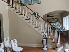 Flowers and greenery for staircase base and garland style arrangements for handrail going up.