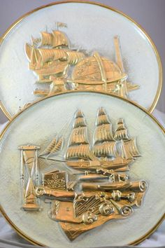 These are a pair of hammered or molded brass explorer galleon sailing themed decorative wall plates. Each plate is 14 inches in diameter and depicts a galleon style ship with explorer devices. The plates have a nice vintage patina and a...