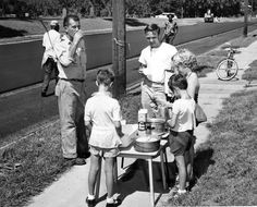 "This road resurfacing crew found an oasis on Sept. 8, 1959, when three young girls began giving away coffee and soft drinks. Cynthia, 8, Kathleen Tollander, 7, and Linda Spain, 8, set up shop on the 6100 block of North 24th Street. Among their customers: Russ Fisher, left, laydown foreman, and Paul Craig, city inspector. ""This type of thing doesn't happen often,"" Craig said, ""but it certainly makes you feel good, and it's appreciated."" THE WORLD-HERALD"