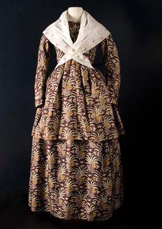 Kostuumjak met lange schoot en rok (met twee splitten in taille, gesloten door haak en oog) van bedrukte zijde met grillig floraal patroon  Vervaardigingsdatum:1846 - 1850  Materiaal:zijde, katoen