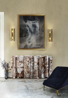 Contemporary interior entrance design ideas with a luxury sideboard, two brass wall lights, a dark velvet lounge chair and a big rectangular rug.