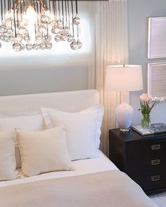 Calm bedroom. Blue walls, white bedding and black brown furniture. I love the light fixture over the bed.