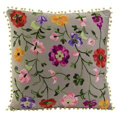 Grey cotton pillow with multicolor floral embroidery and pom pom trim.  Product: PillowConstruction Material: Co...