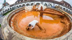 Mitarbeiter einer Entsorgungsfirma schöpfen in Bad Nauheim (Hessen) rötlichen Schlamm aus dem Brunnen im Sprudelhof.