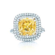 Square Fancy Intense Yellow diamond ring in platinum with white diamonds.