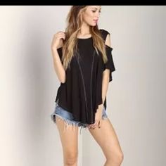 Free people top Free People top with shoulder cut outs. Lose fitting with white stitching down the front. One flaw a little tear on the left shoulder cut photo of flaw listed. Says XS but fits like a small/med. Free People Tops Tees - Short Sleeve