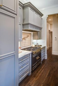 Gorgeous gray and white kitchen boasts a La Cornue CornueFe Range fixed against linear honed marble backsplash tiles beneath a brass swing arm pot filler mounted to cream mosaic cooktop tiles positioned under a light gray paneled hood.