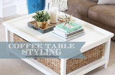 coffee table styling. love the use of baskets on the bottom shelf.Great for storage.